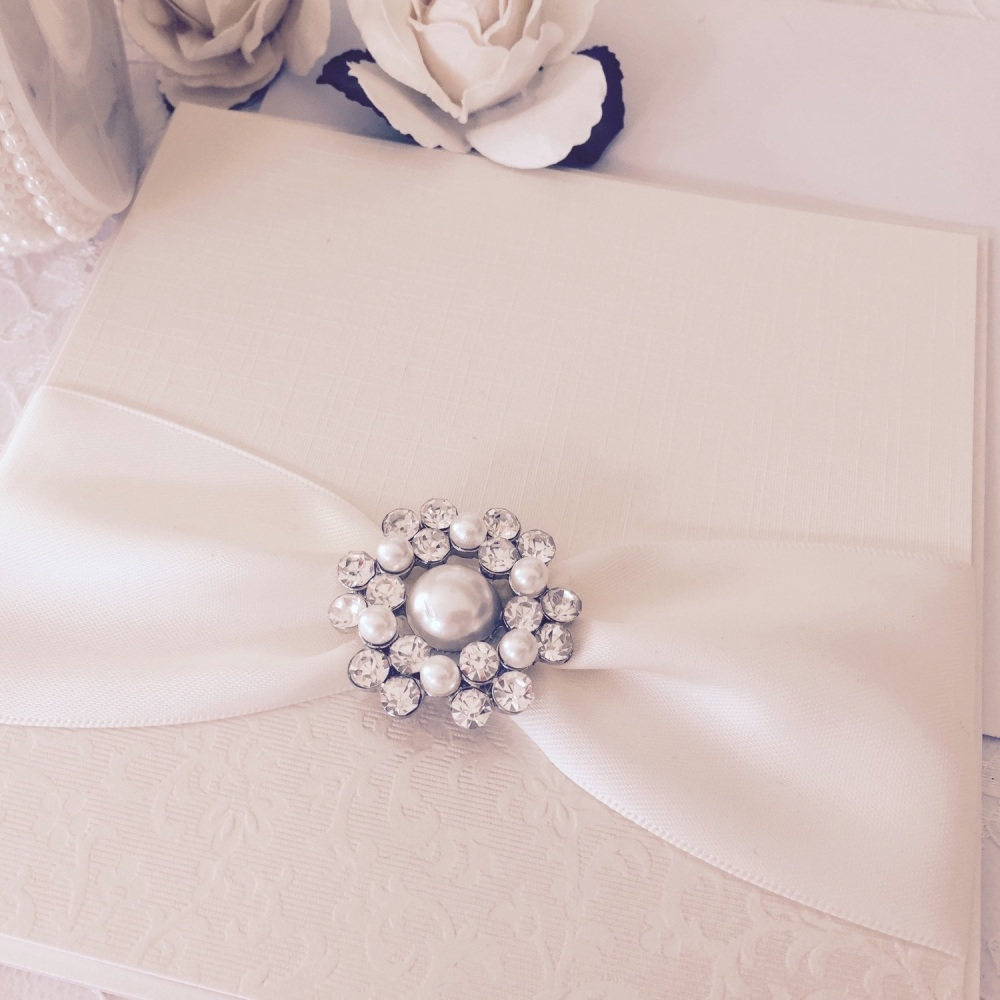 Vintage wedding invitation with pearl brooch