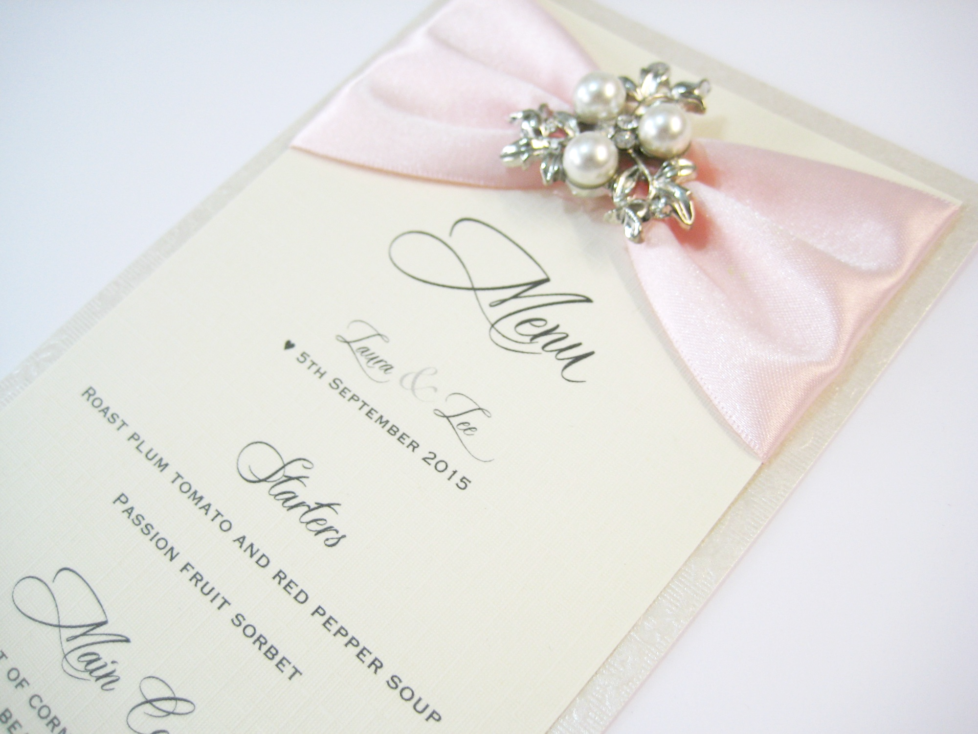 wedding breakfast menu with blush pink ribbon and pearl