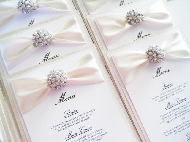 Champagne wedding breakfast menu with crystal brooch and ribbon