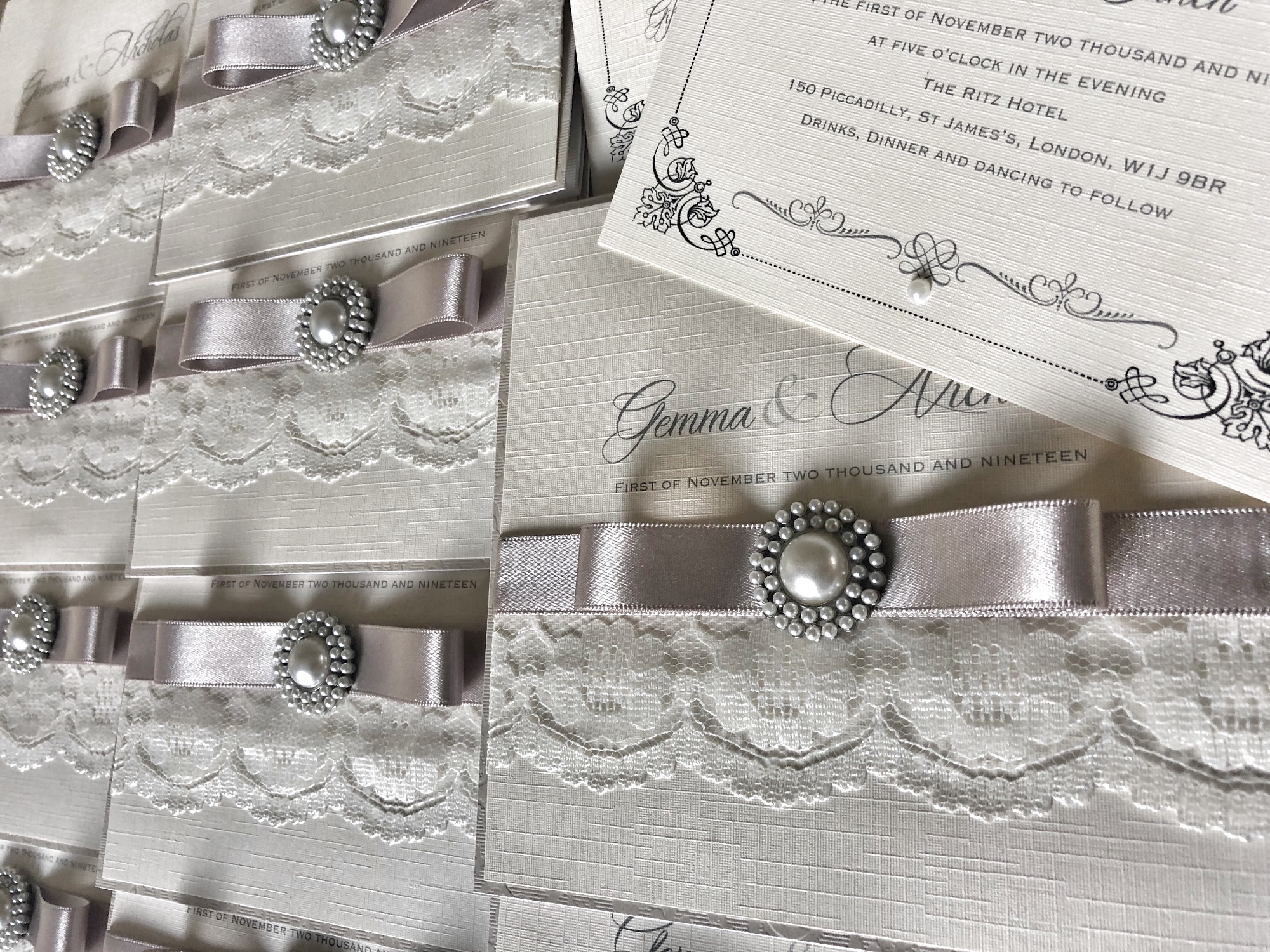 Lace wedding invitations in ivory and silver with pearl brooch