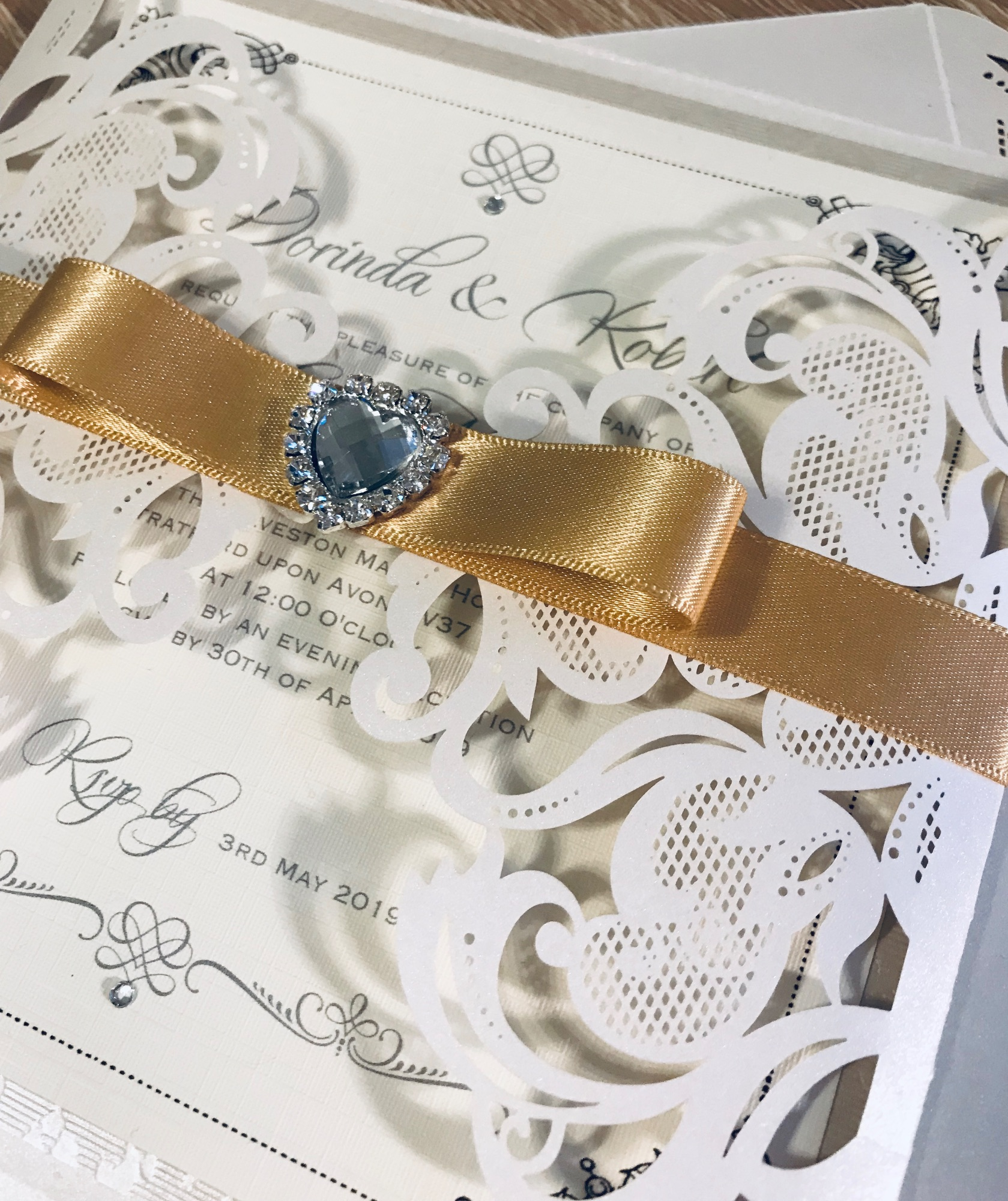 Laser cut invitation with gold ribbon