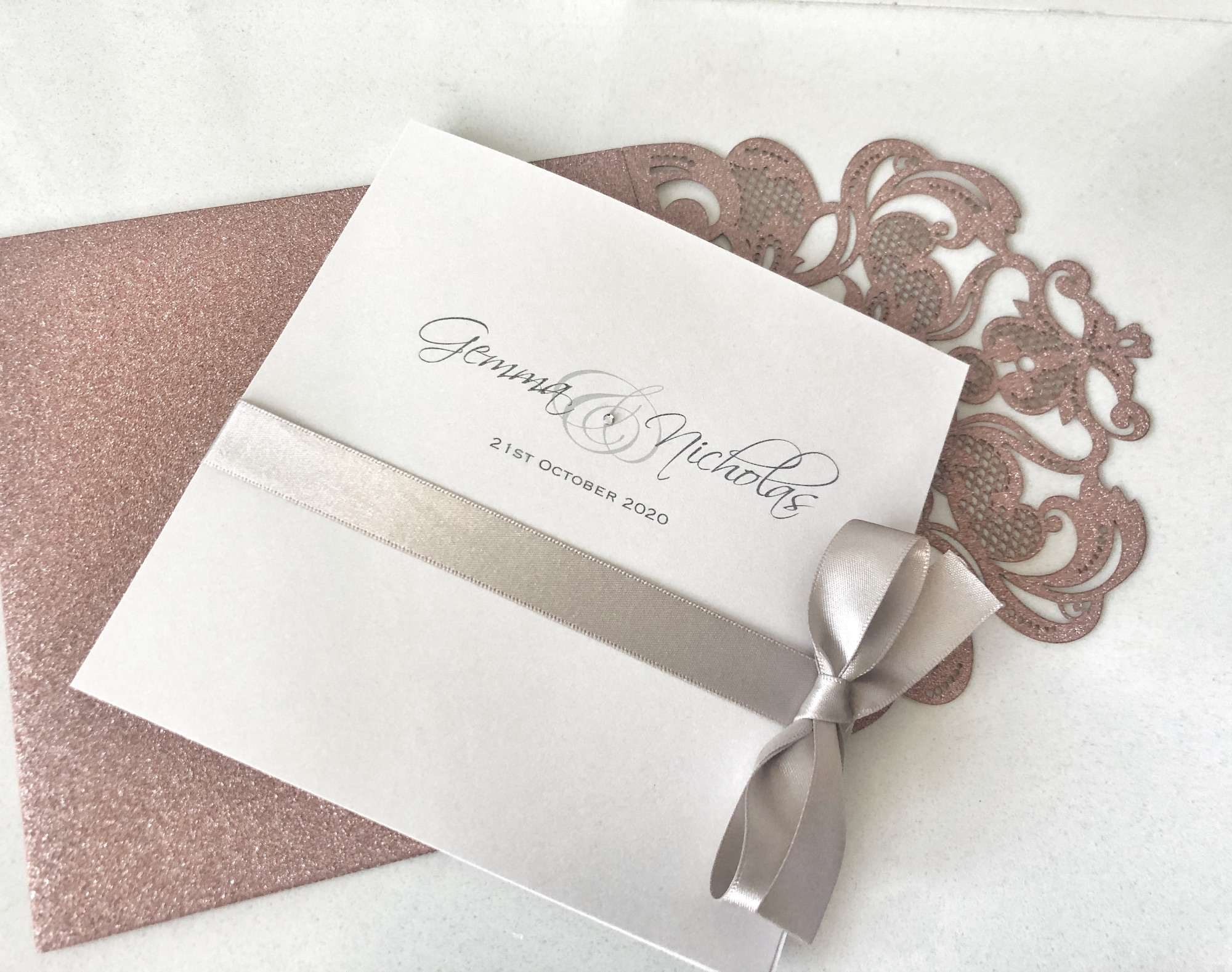 Pearlised ivory wedding invitation with silver bow