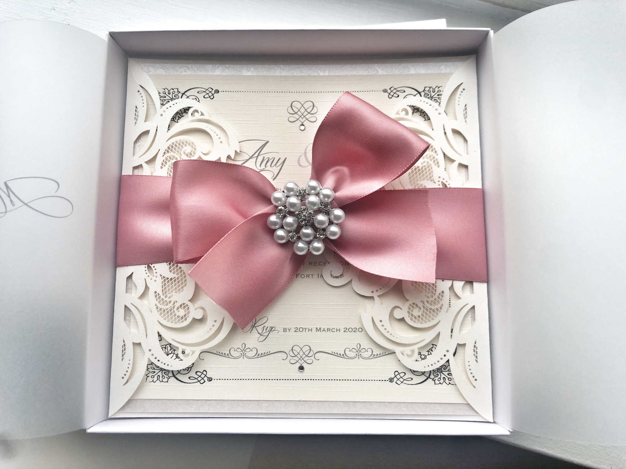 Laser cut invitation with large bow and pearl brooch