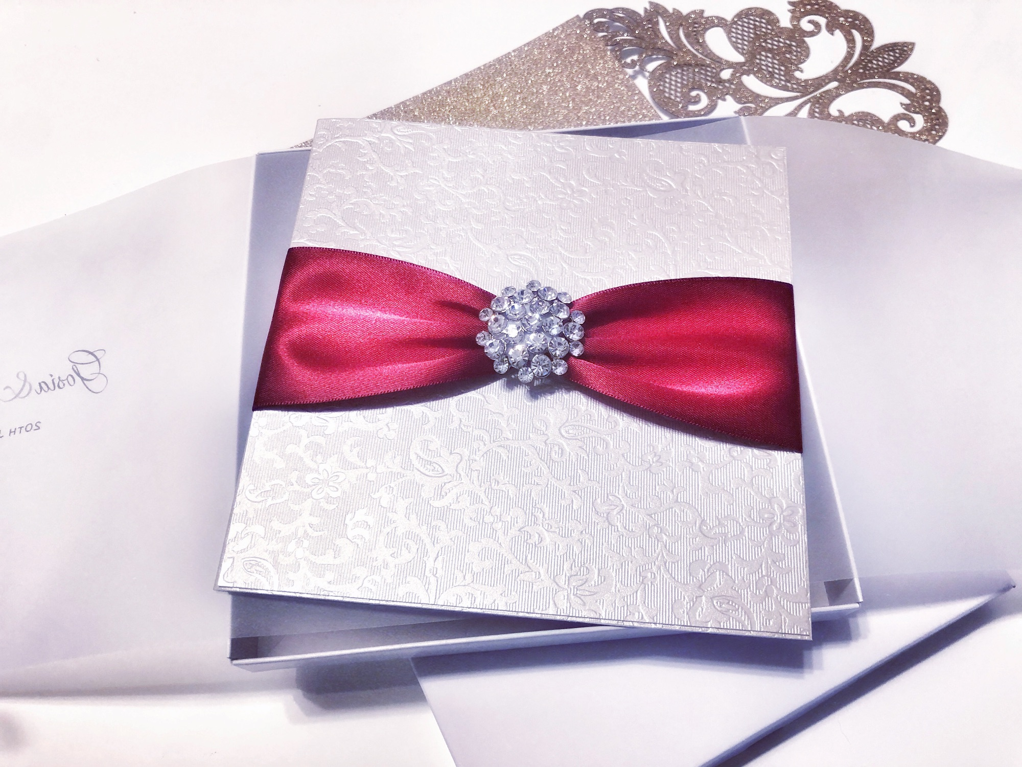 Crystal invitation with red ribbon in box