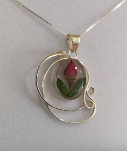 Rosebud necklace surrounded by a Sterling silver swirl