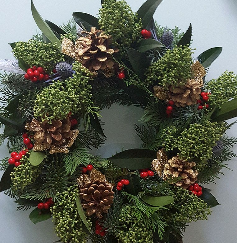 Gold ribbons and acorns with skimmia, sea holly and berries.
