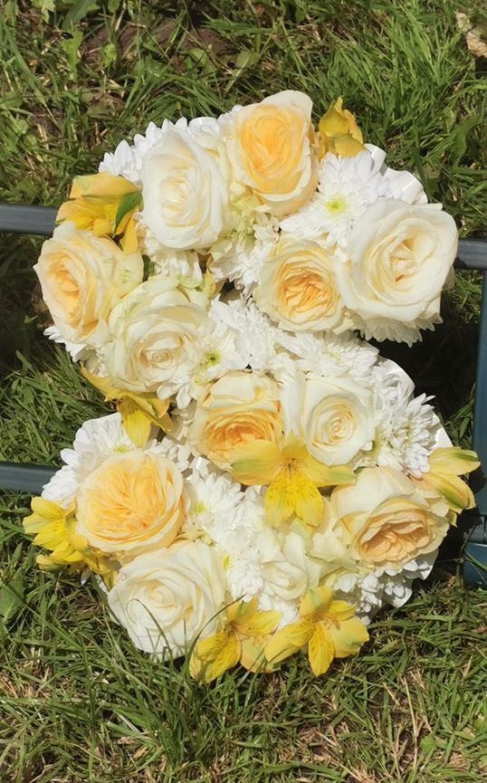 Funeral lettering with buttercup roses, white rose and alstroemeria