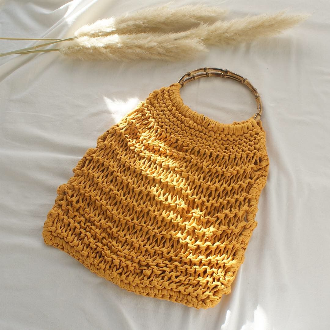 Yellow knitted handbag with bamboo handles by Elisha Francis