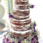 Chocolate naked cake with purple flowers