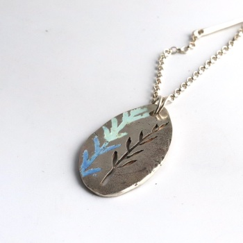 Solid Silver Long Oval-shaped Pendant with Cut-out and Enamelled Leaf Design with Embellished Silver Chain.