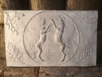 Moonlight boxing hares wall sculpture, waxed cast stone