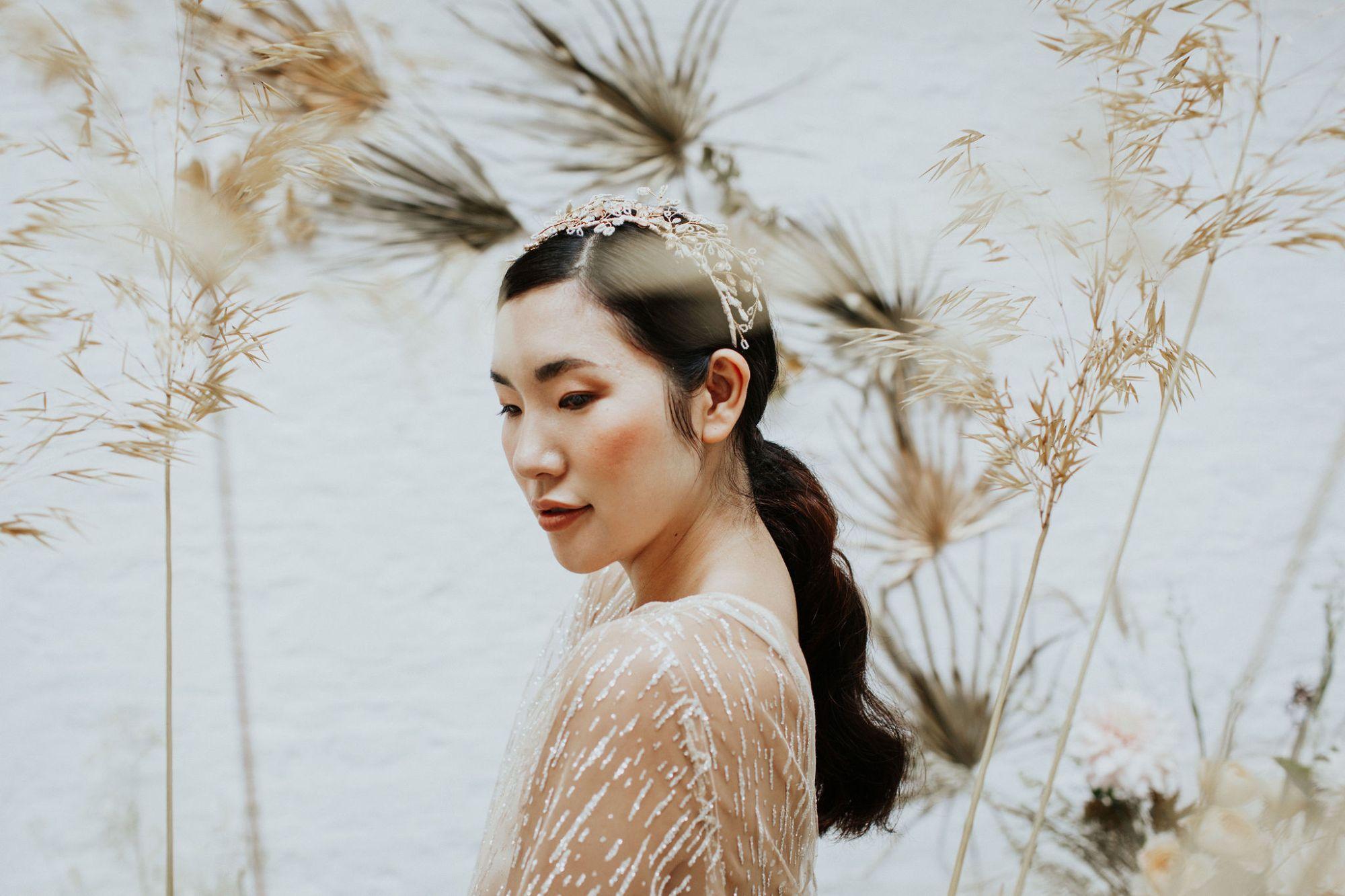 A model wears a delicate beaded bridal headdress handmade by Clare Lloyd Accessories
