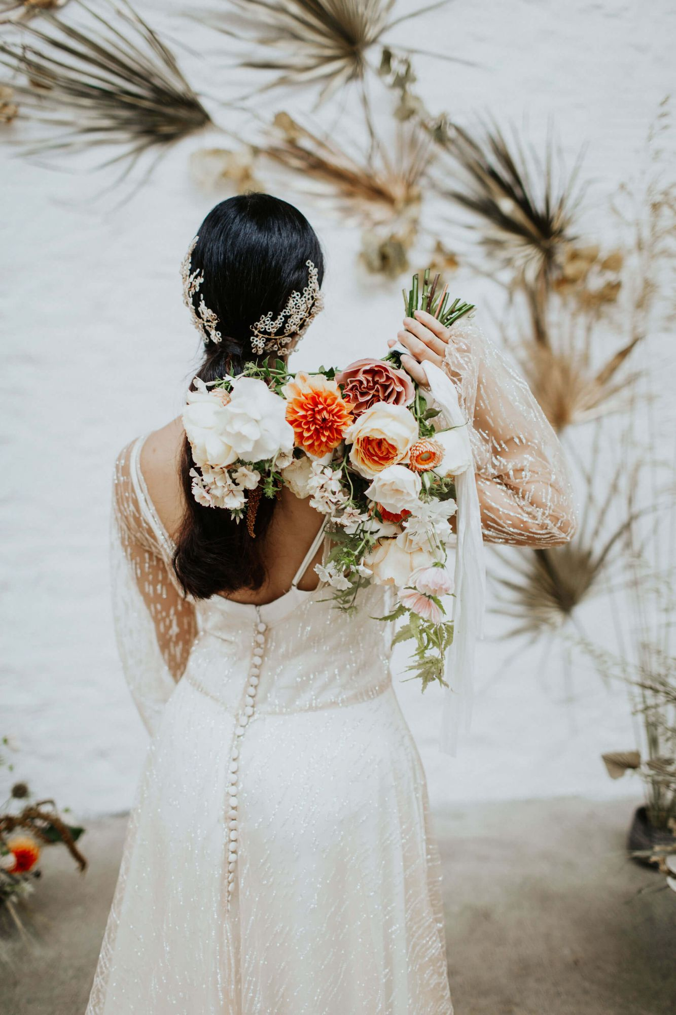 A model stands with her back to us. She has a bouquet of ivory and coral flowers over her shoulder, she is wearing a Rachel Burgess Bridal Boutique wedding gown of gold glittery lace and is wearing a delicately beaded bridal headpiece made by Clare Lloyd Accessories