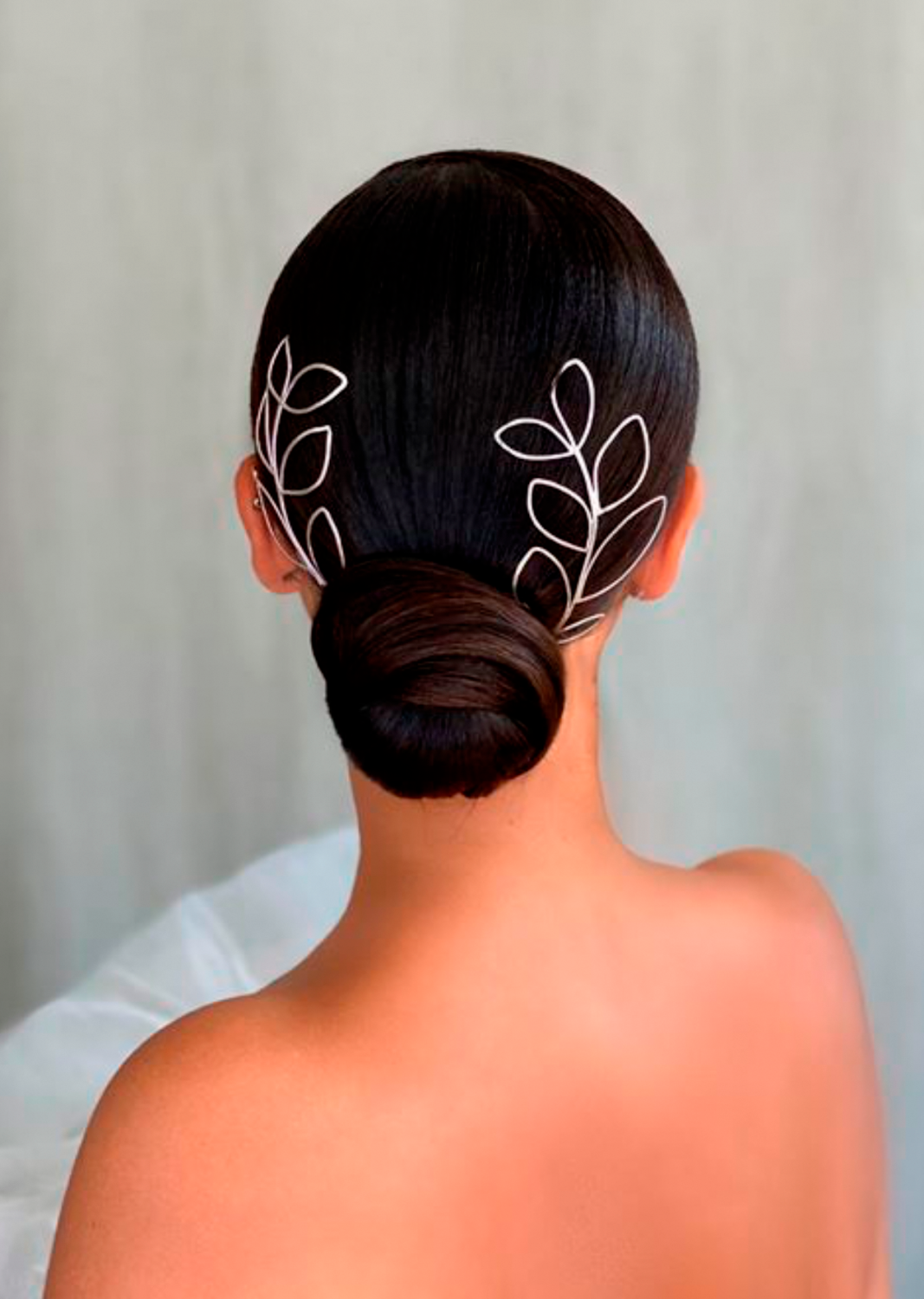 Low bridal bun created by Kasia Fortuna featuring two silver leaf headpieces