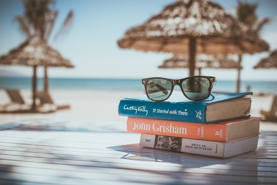stack of reading books and sunglasses on a beach holiday