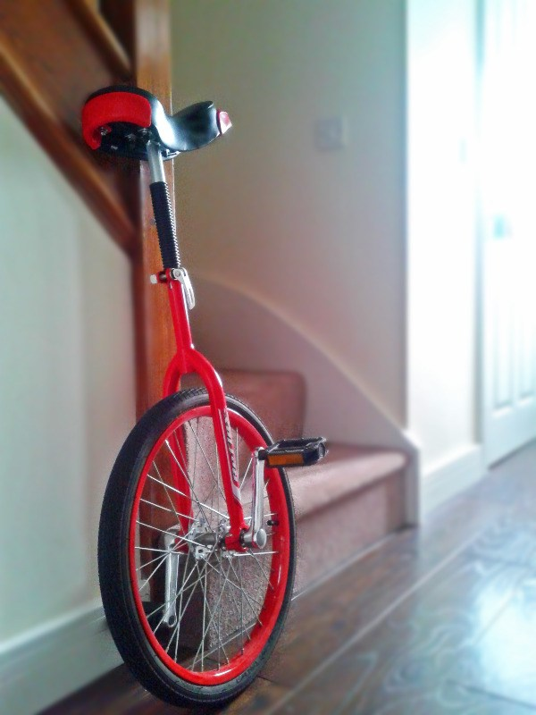 Red Unicycle In Hallway