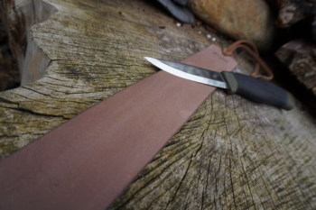 Sharpening-old field strop in Mink length ways with Mora knife