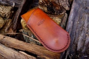 cutting hand stitched mini saw sheath in saddle tan for beaver bushcraft