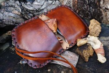 leather hand tooled pioneering tinder pouch open with tinder by beaver bush