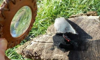 Fier and leather solar pendant in action for beaver bushcraft with char clo
