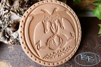 Leather patch embracing dragons made by beaver bushcraft