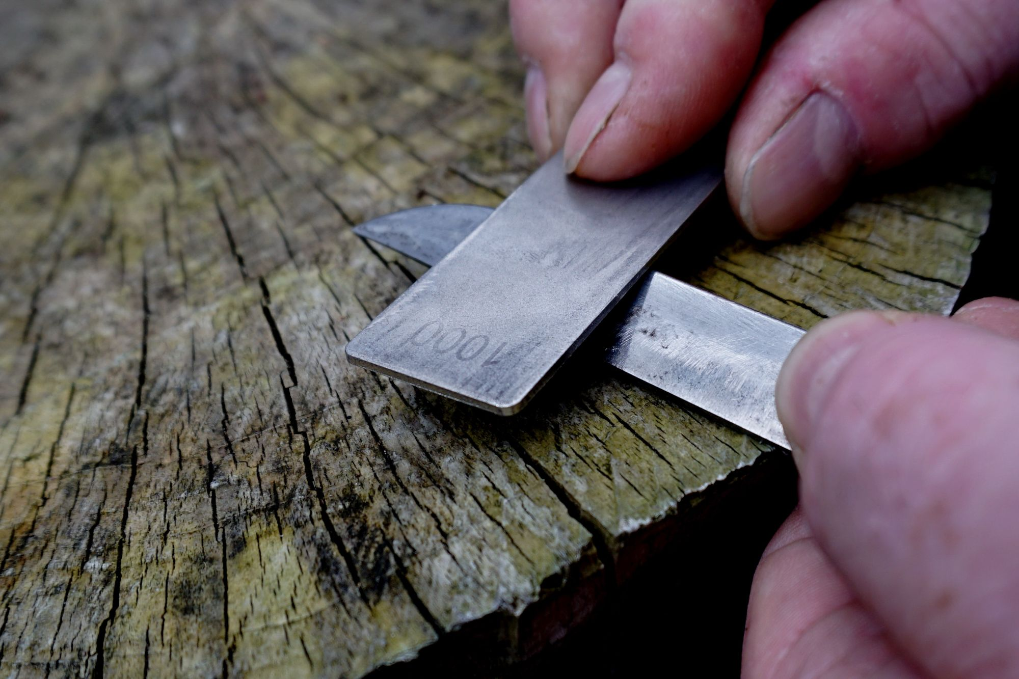 Scrubbing the blade with the  180 grit side of  the diamond whetstone