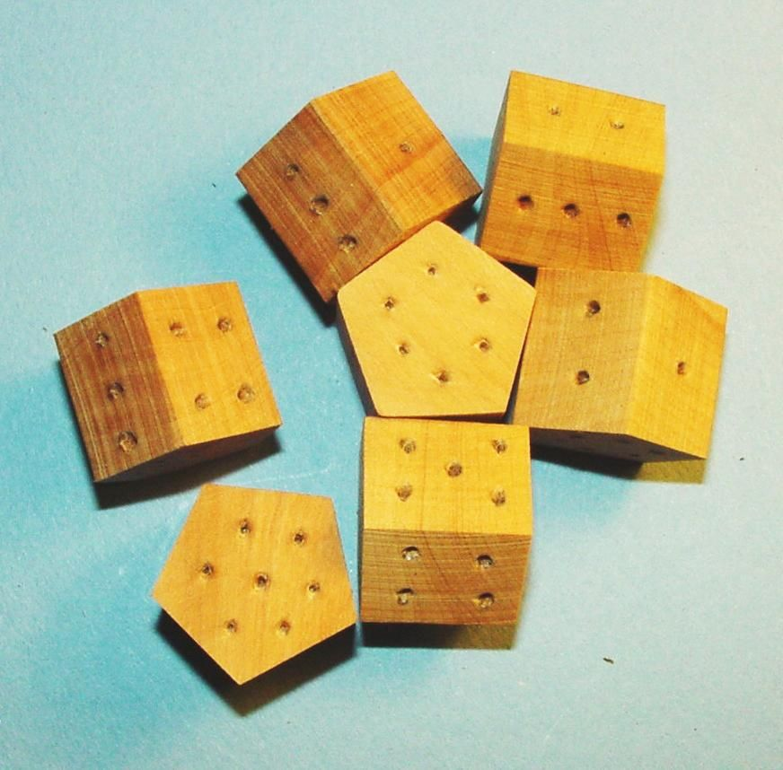 Several oak seven-sided dice from The Historic Games Shop