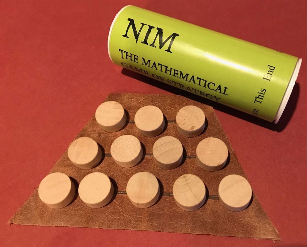 Nim game set out; leather board and wooden pieces, with storage tube