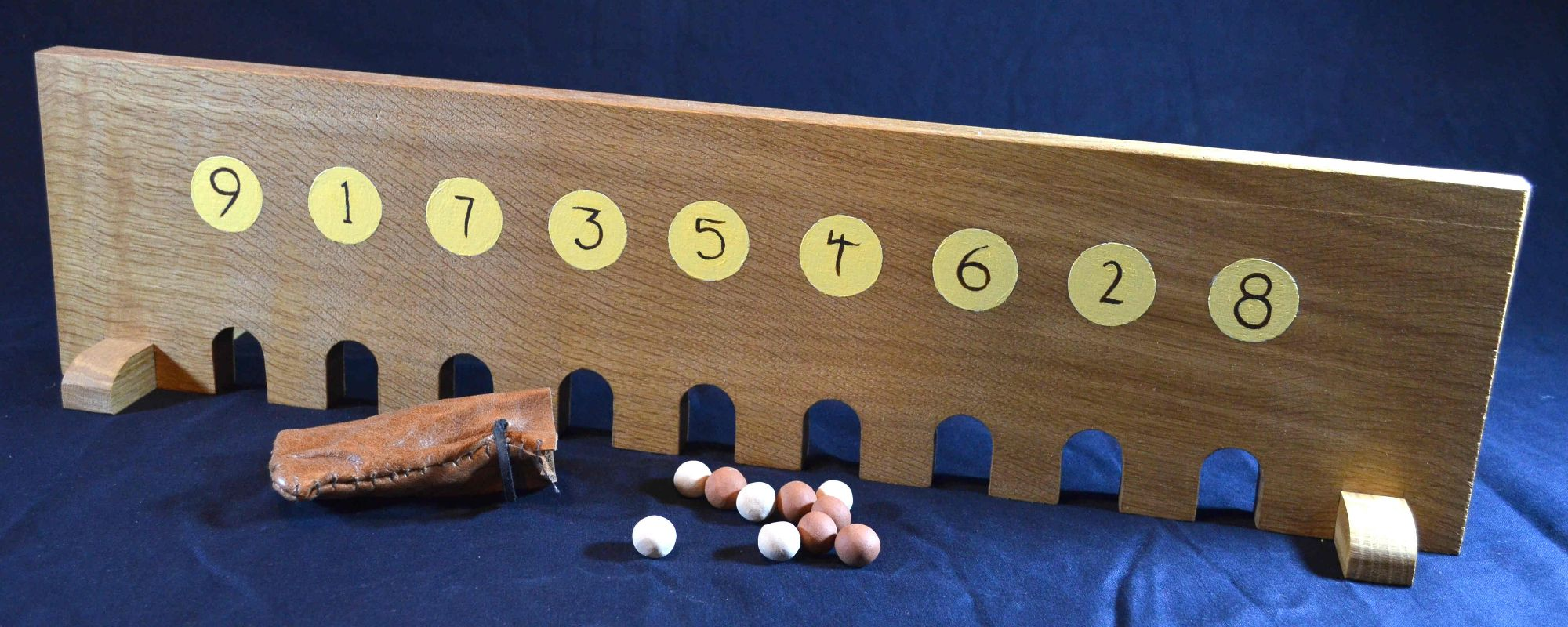 Troll Madam, oak board with nine numbered arches and leather pouch of fired clay marbles