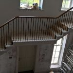 sweeping oak handrail and bespoke metal spindles