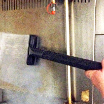 This commercial steam cleaner with vacuum is cleaning a stainless steel canopy in a commercial kitchen