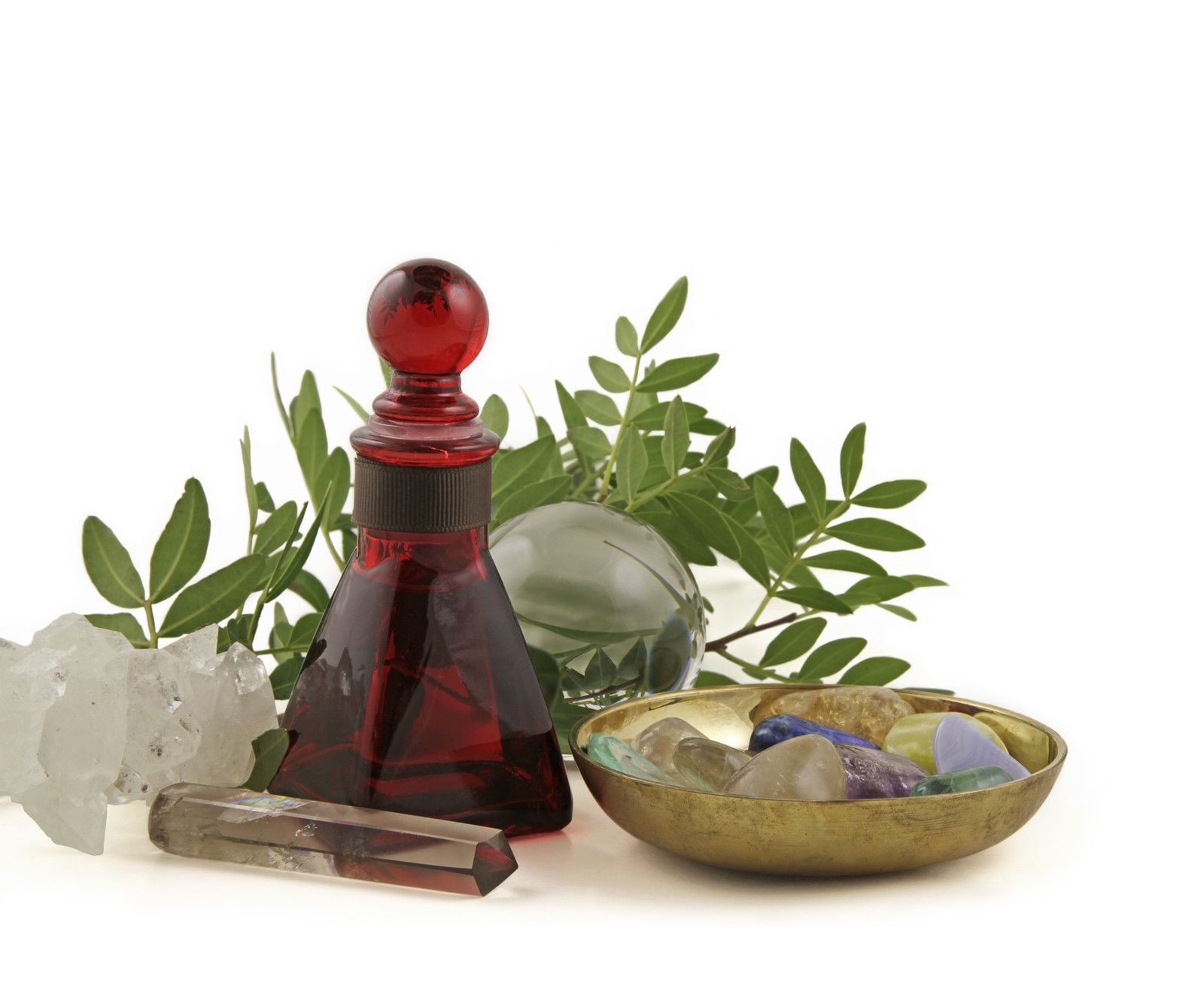 red bottle, massage wand and dish of crystals