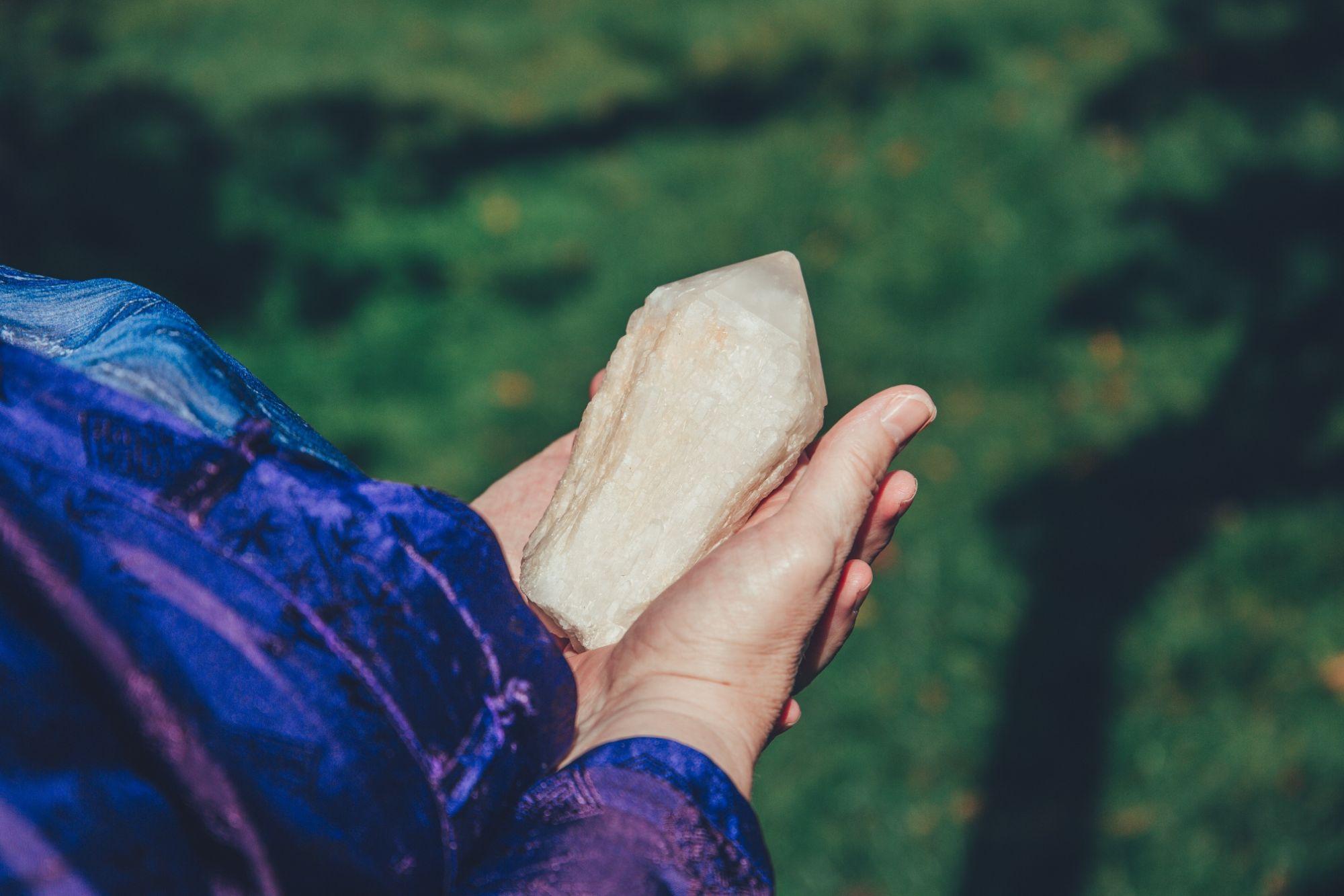 Helen's hands holding a candle quartz point