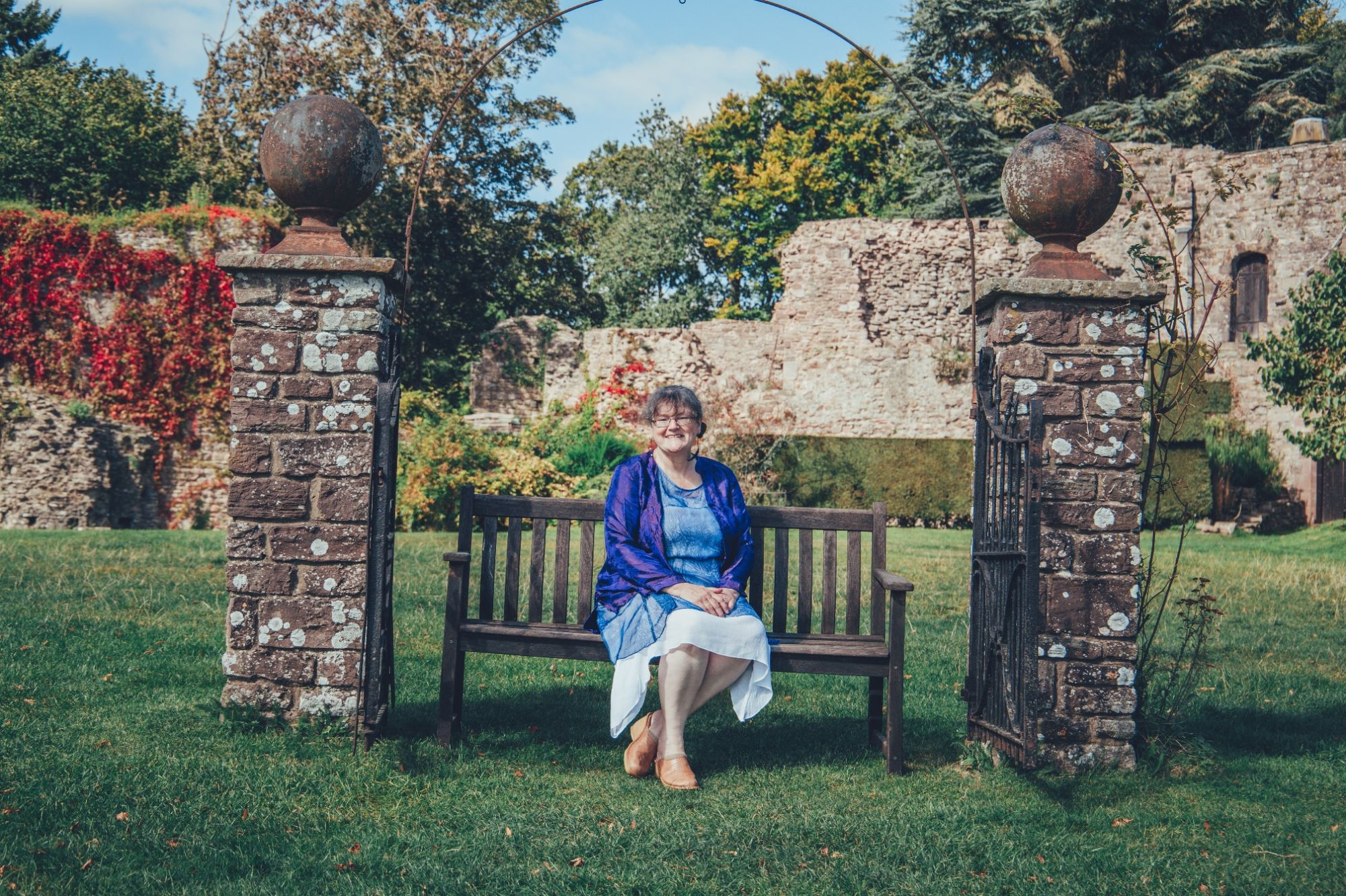 Helen sitting on  a bench at Usk Castle