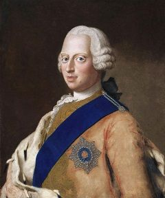 Frederick in a white wig with a tan coat and blue sash