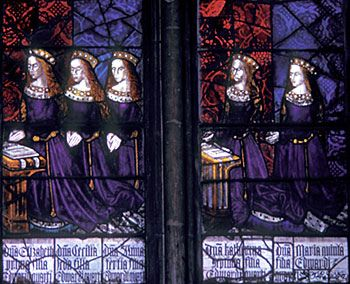 A stained glass window depicting five of King Edward 4th's daughters, kneeling in prayer.