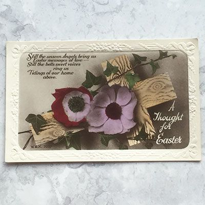 A postcard with two flowers in pink and violet and wooden cross.