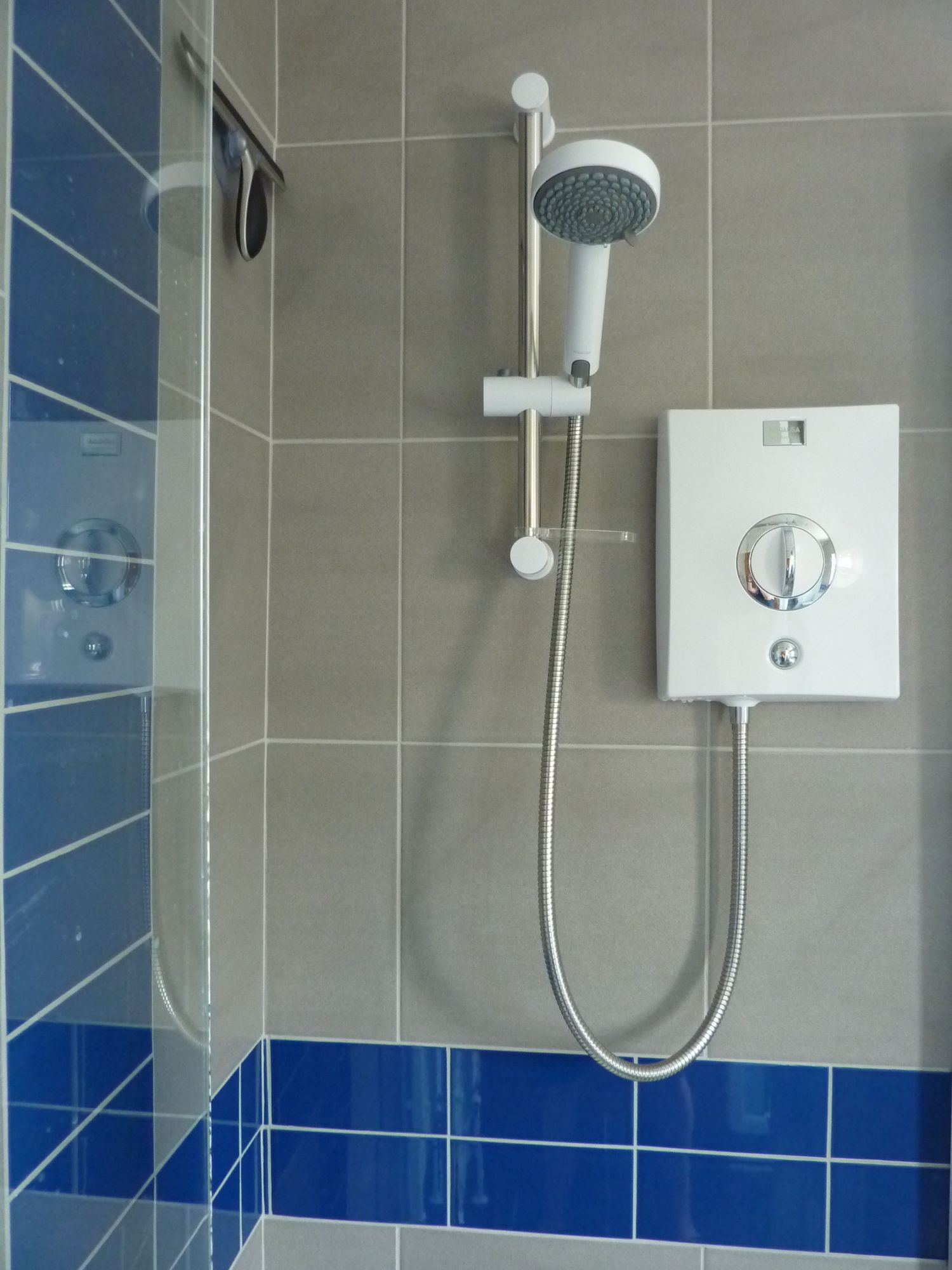 electric shower grey tiles blue brick pattern tiles
