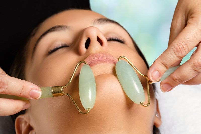 woman receiving facial massage with jade rollers