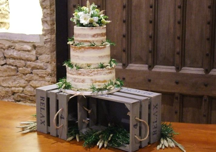 semi naked wedding cake on wooden crates.