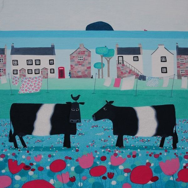 Belted Galloway cattle graze infront of a small coastal village in Scotland.