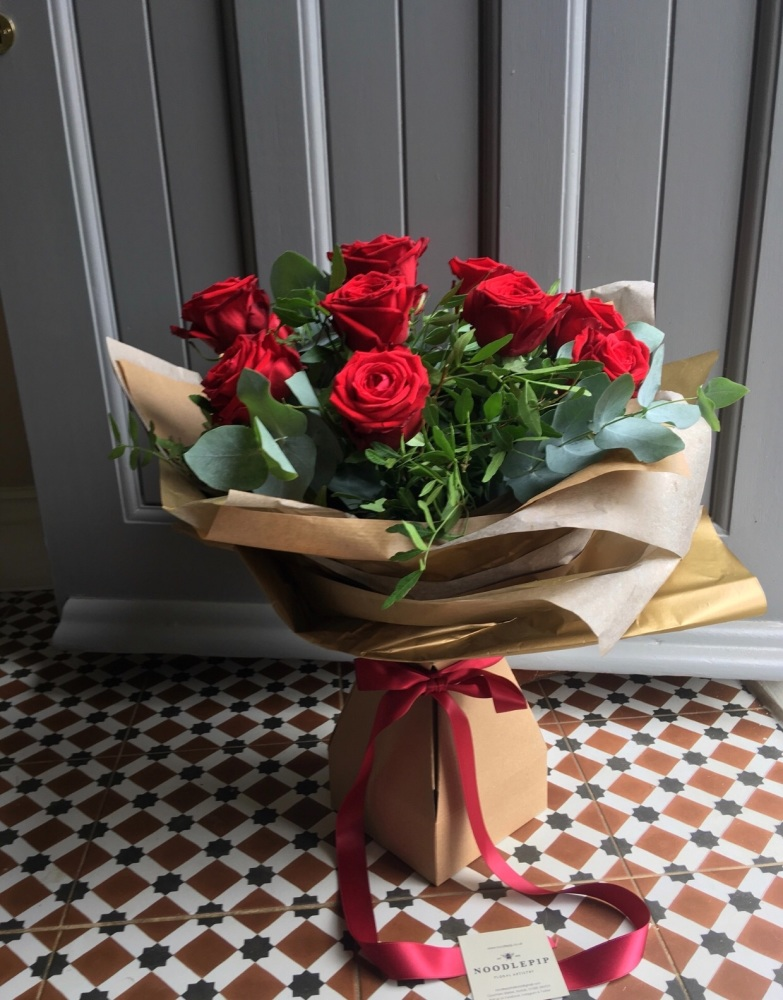 A dozen red roses in a water box