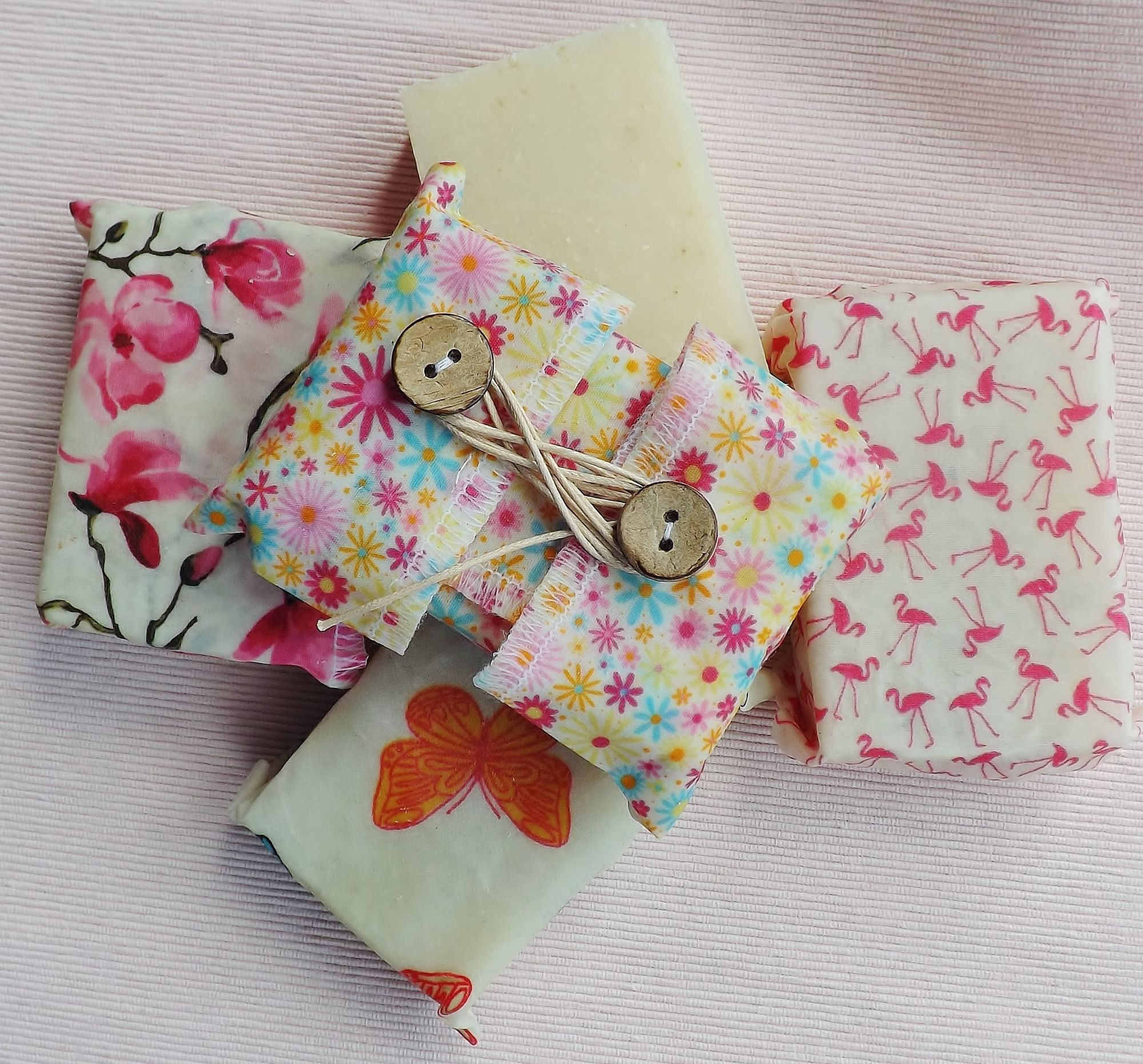 V-Eco Pamper Packs,  a collection of five small bars of soap with four of them wraps in waxed fabric with floral, butterlfy and flamingo designs
