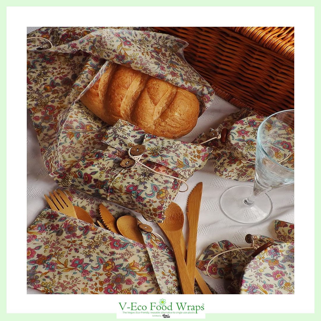 "LoafLoverâ""¢ covering a loaf next to a hamper basket and bamboo cutlery which is  in a waxed pouch"
