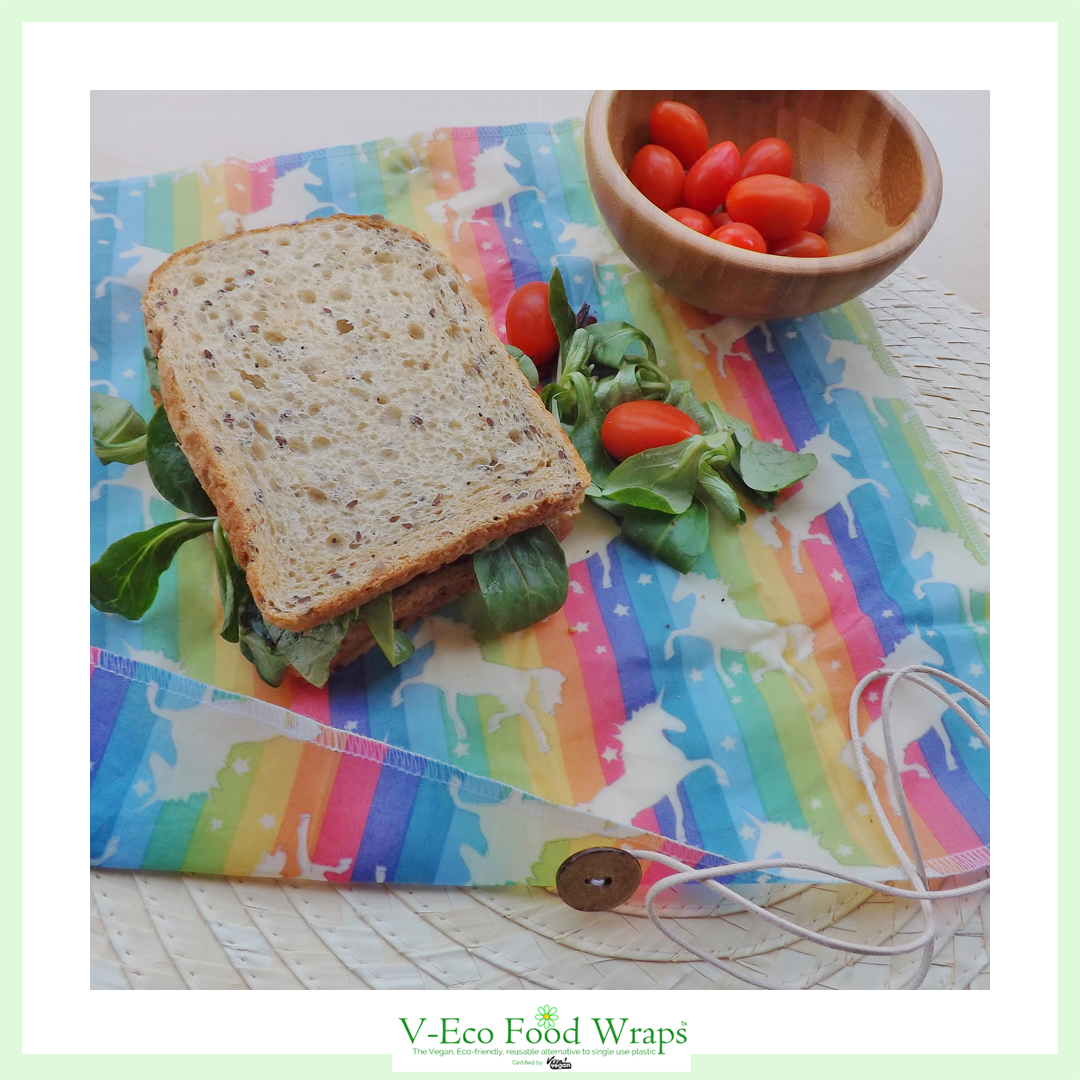 "a salad sandwich laying on an open ButtyWrapâ""¢  in unicorn fabric with a bowl of plum tomatoes next to it"