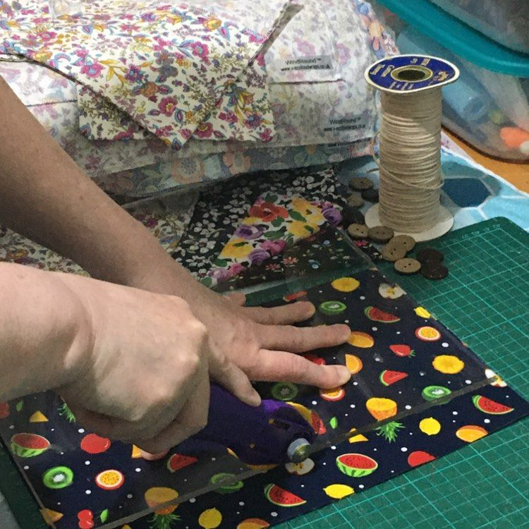 Mixed fruit fabric being  cut with a rotary cutter with pouches and a reel of cord in the background, V-Eco Home