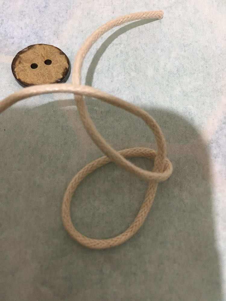 A part-formed knot of cotton cord with a coconut button, V-Eco Home