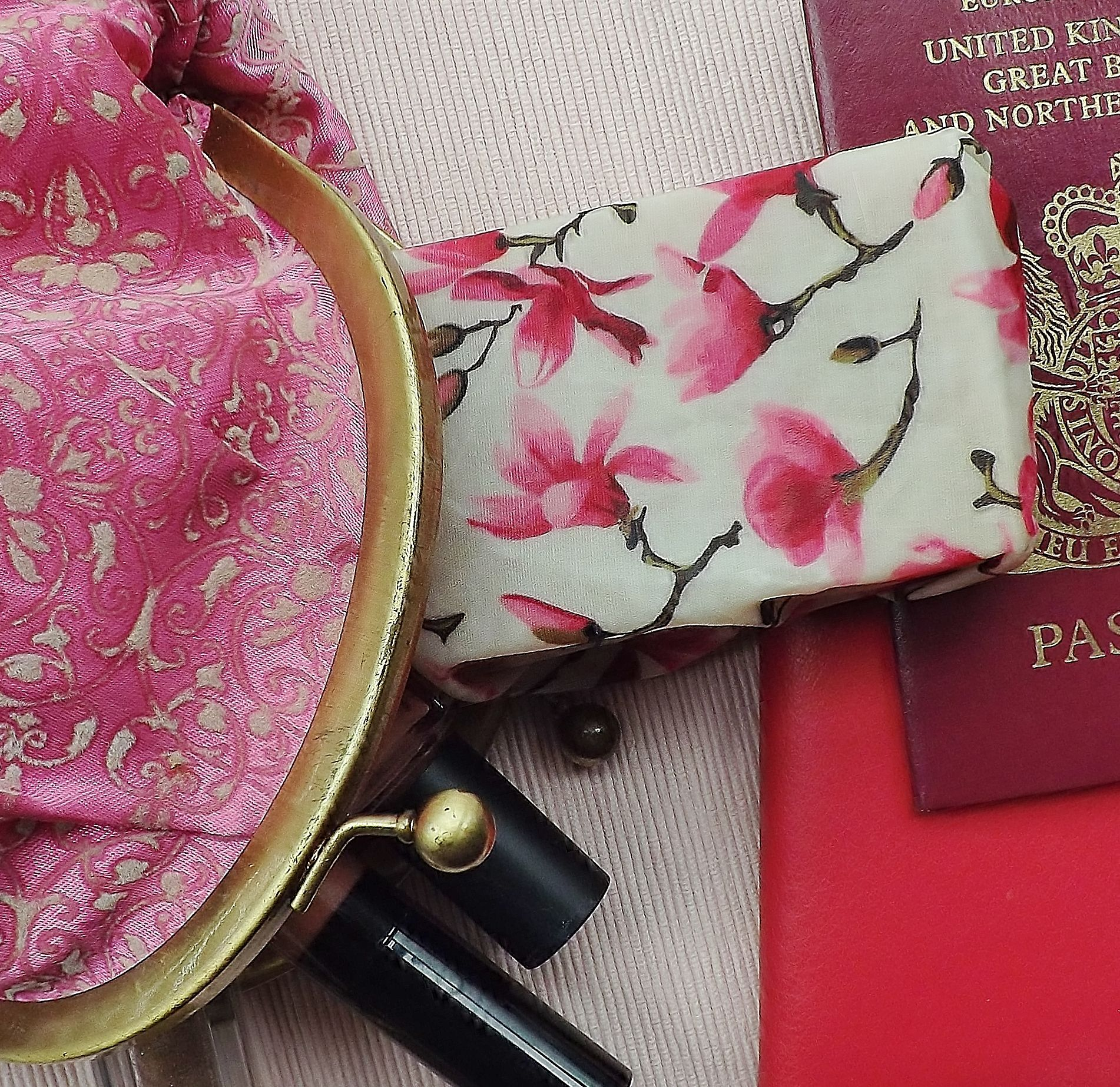 """V-Eco Pamper Packsâ""""¢,  SoapSaverâ""""¢ wrapped around a bar of soap alongside a cosmetic bag and passport"""