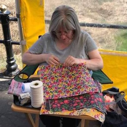 Woman sewing colourful fabric with sewing needles and thread next to her