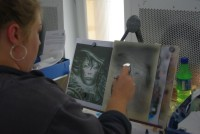 student airbrushing portrait